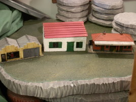 Single story comparison. Dapol's OO scale garage and ticket hall bracket the Warbases modular building.